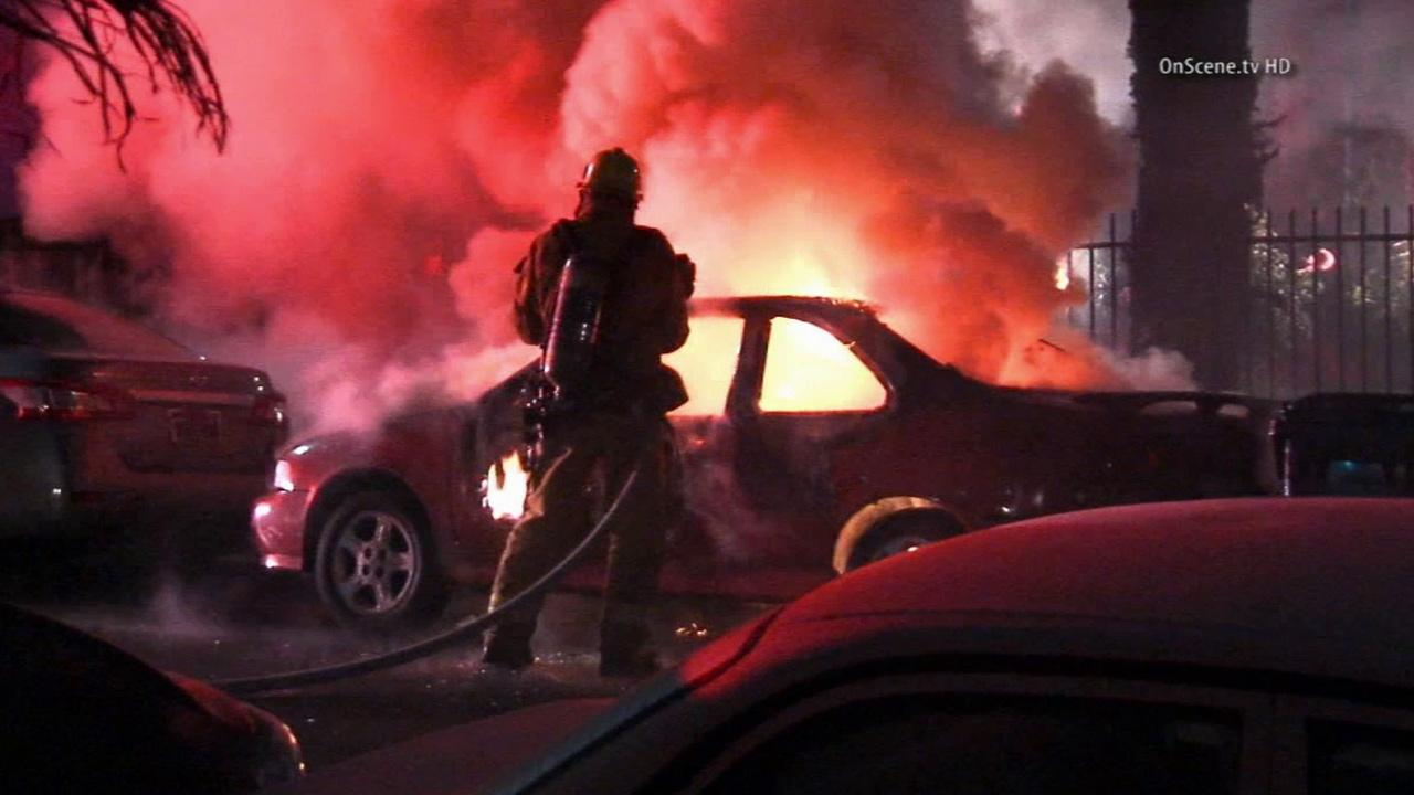 A firefighter attempts to put out a suspicious fire in a car parked in South Los Angeles on Thursday, April 17, 2014.