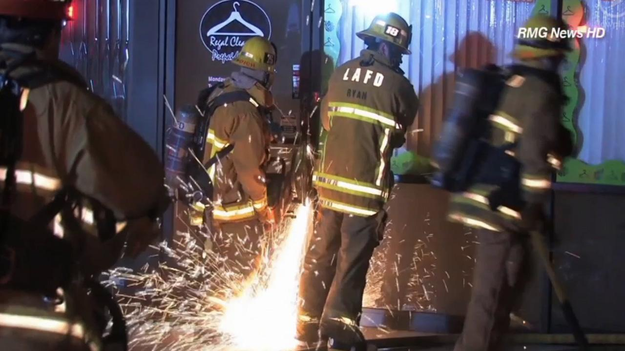 Firefighters break down a door to check the store for a fire that started in a strip mall in Granada Hills on Thursday, April 24, 2014.