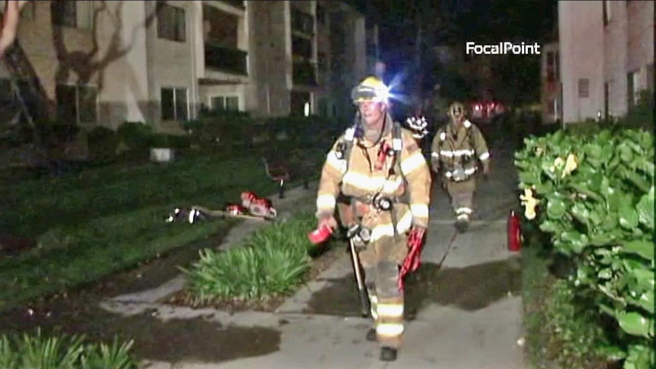 Firefighters are seen at a Rossmoor apartment building where a fire broke out Monday, July 9, 2012. Two off-duty officers were credited with helping evacuate people from their units during the fire.