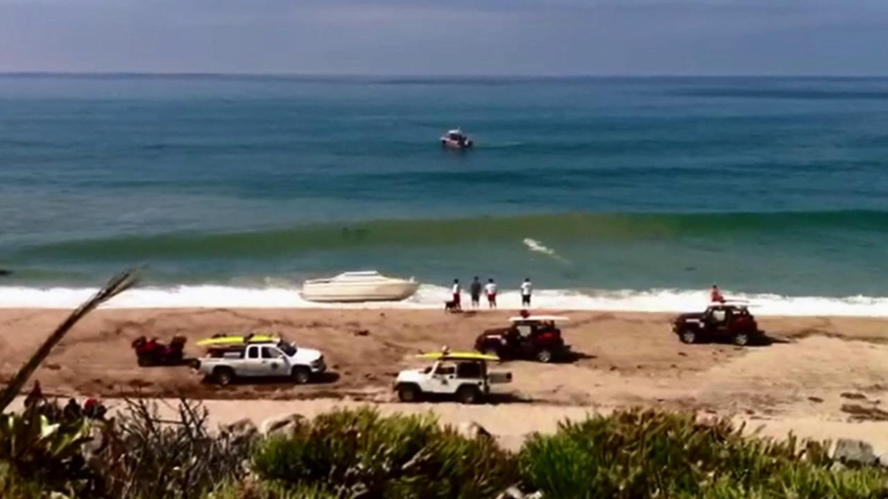 Law enforcement officials are seen at a beach in Orange County, where a boat came ashore with 10 suspected illegal immigrants on board on Monday, Sept. 17, 2012.