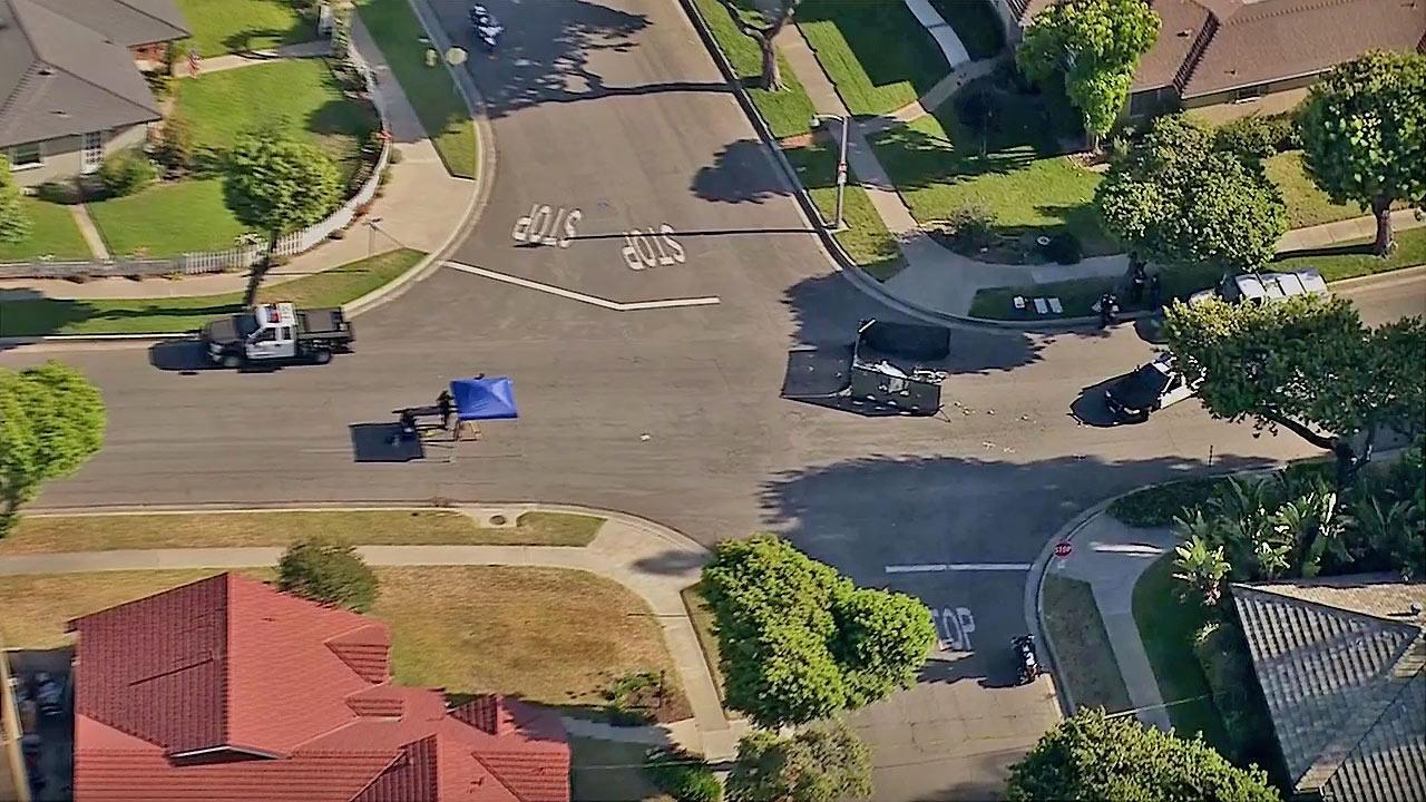 Police set up a perimeter around the covered body of a female bicyclist who was struck and killed by a FedEx truck in Fullerton Thursday, June 20, 2013.