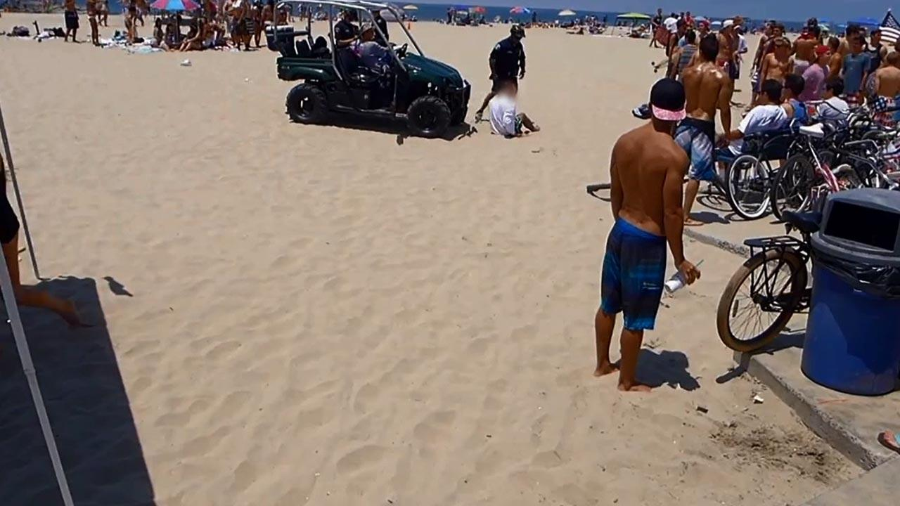 Newport Beach police arrest an unidentified person on the beach on Thursday, July 4, 2013.