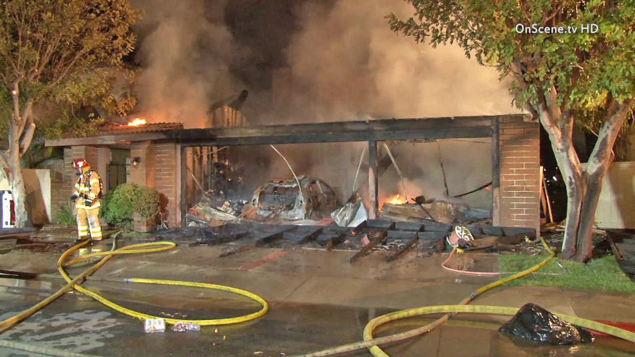 A home in Irvine is seen on fire Tuesday, July 30, 2013. The family and their dog (seen right) escaped.