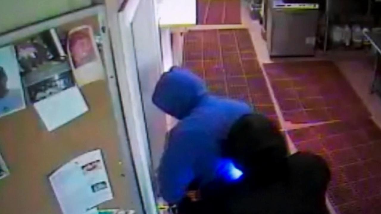 Two men police suspect of being involved in a string of crimes across Orange County try to open a door in an alleged attempt to steal liquor in this undated file photo.