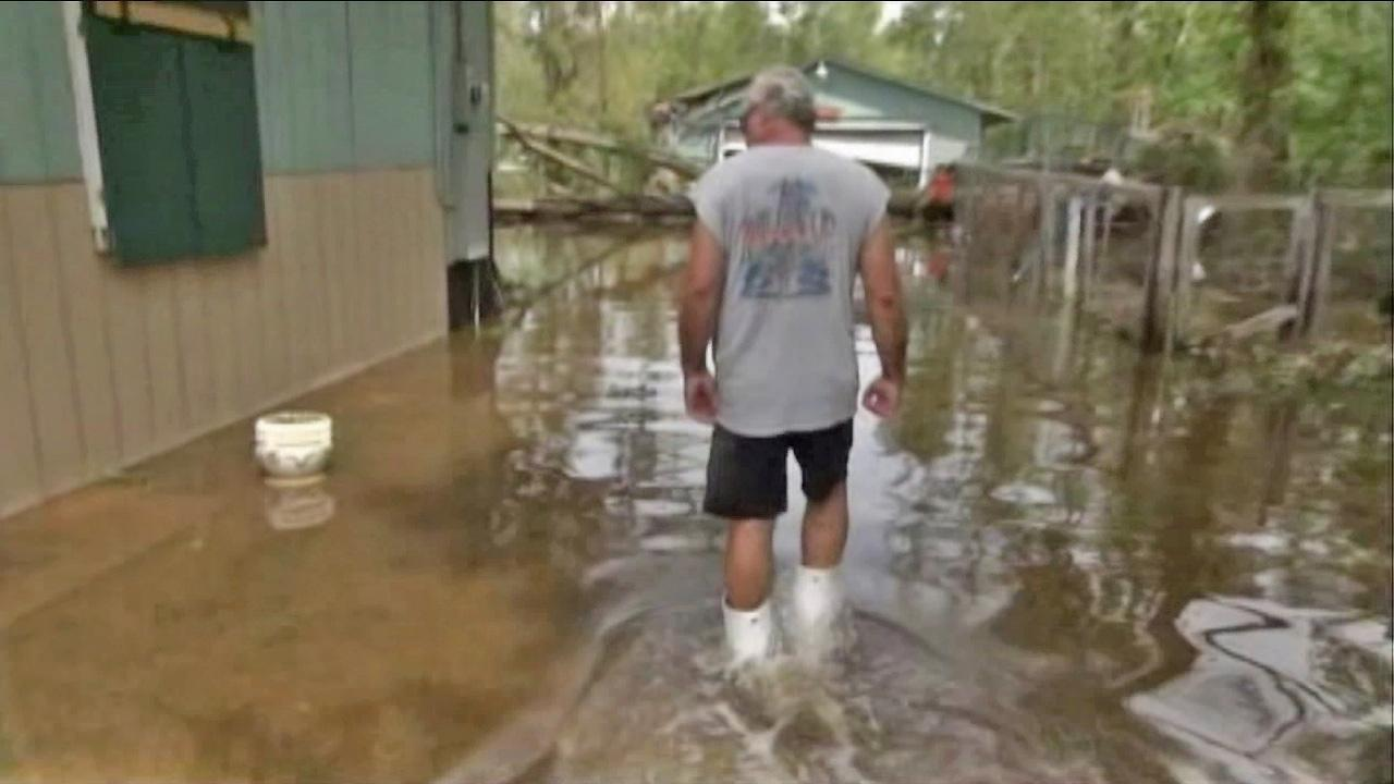 A man is seen wading through a flooded neighborhood following Hurricane Isaac in this undated file photo.