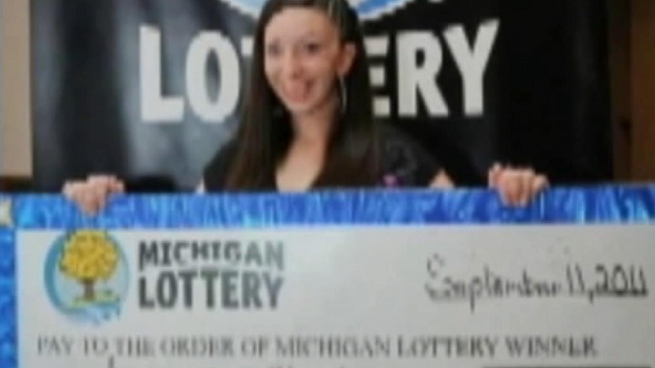 A woman who won the lottery in Michigan is shown holding her jackpot check for $1 million.
