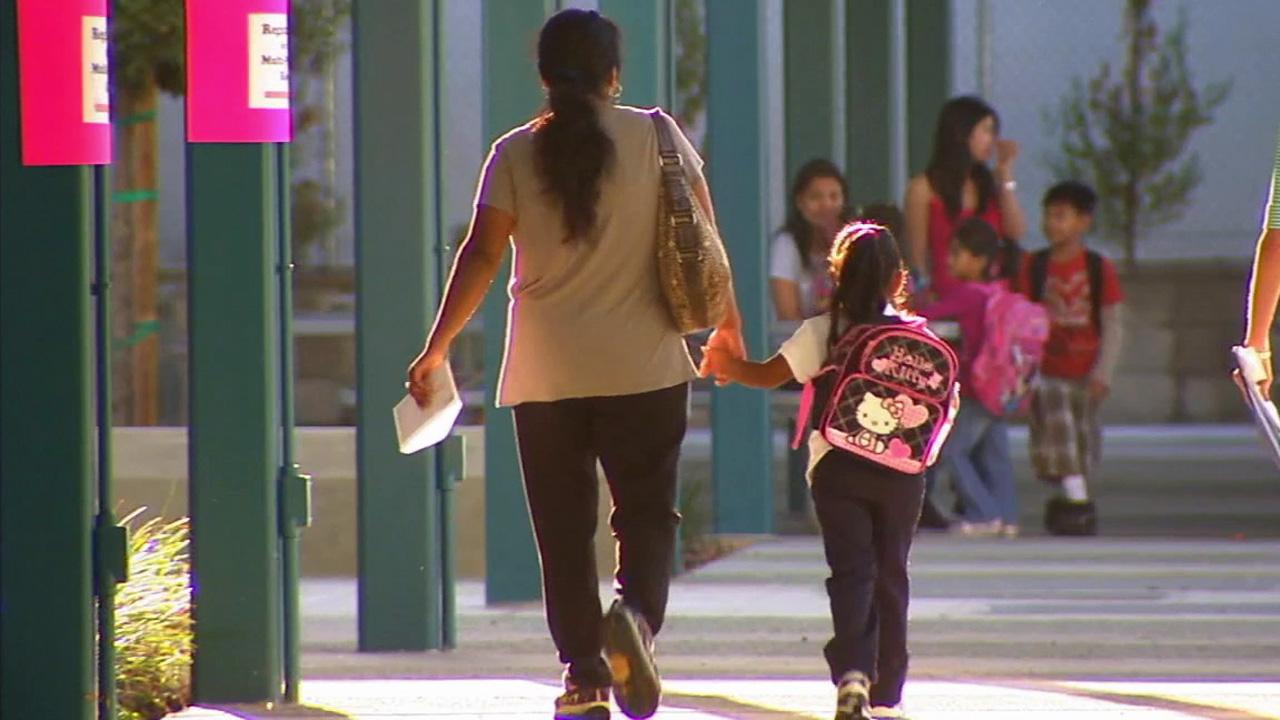 An adult walks a young student in this undated file photo.