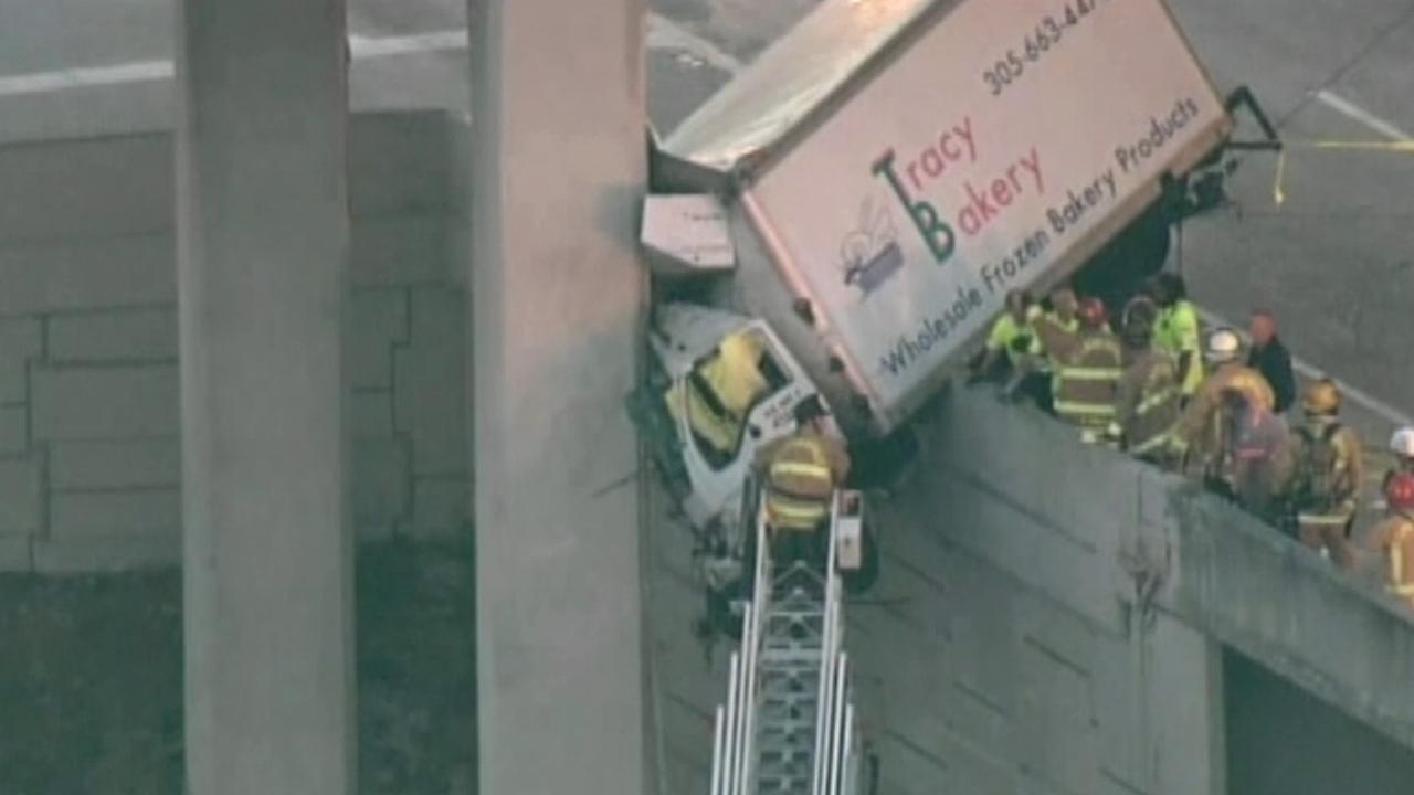 A bakery delivery truck is shown dangling off the side of an overpass ramp in Florida on Wednesday, Feb. 06, 2013.