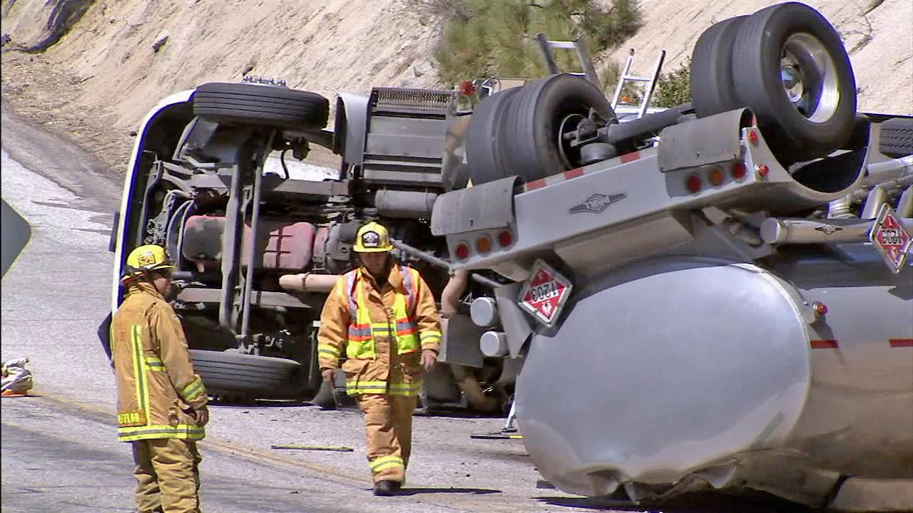 Firefighters examine an overturned tanker that was transporting fuel when it flipped over in Angelus Oaks on Friday, April 26, 2013. The accident shut roads and caused a hazard to the nearby Santa Ana River Basin.