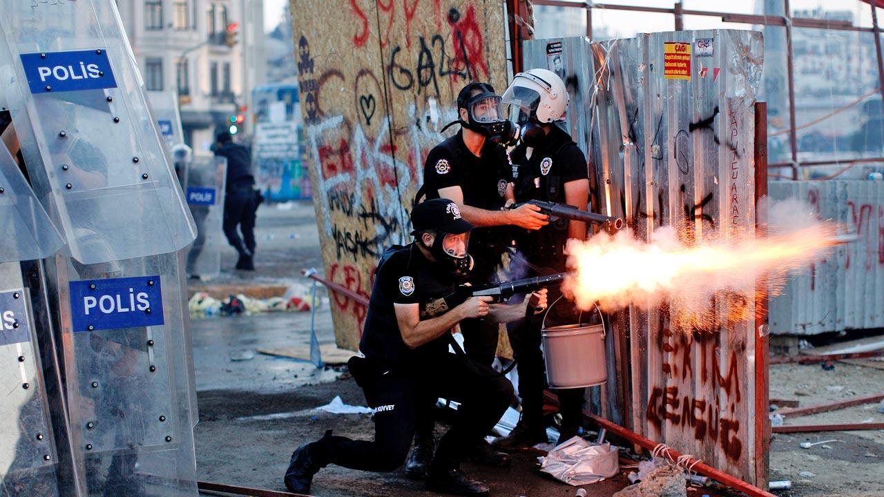 A riot policeman launches a tear gas canister during clashes in Taksim square in Istanbul, Tuesday, June 11, 2013.