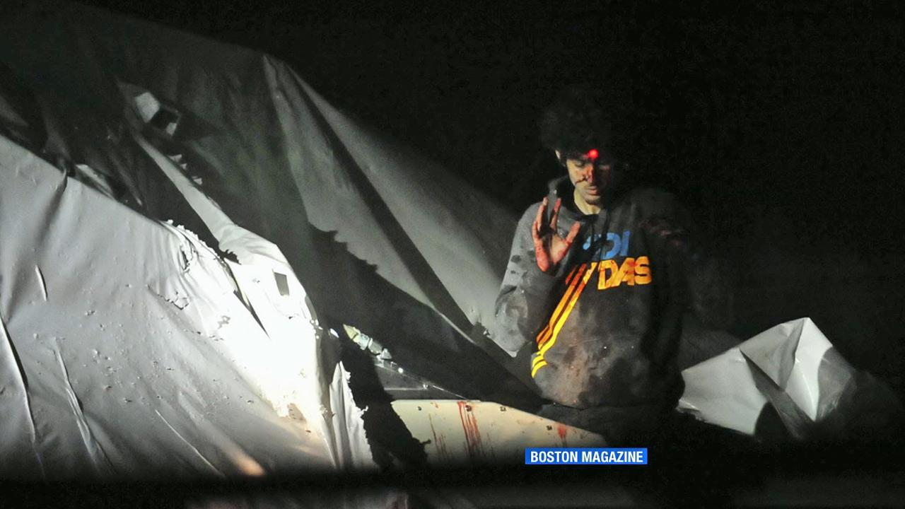 Boston Marathon bombing suspect Dzhokhar Tsarnaev emerges from a covered boat as a sniper trains a laser target at his head.