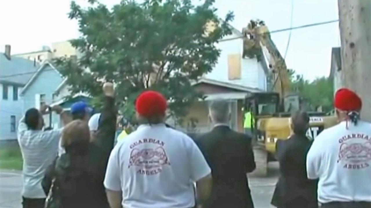 Spectators watch as Ariel Castros house is torn down in Cleveland Wednesday, Aug. 7, 2013.