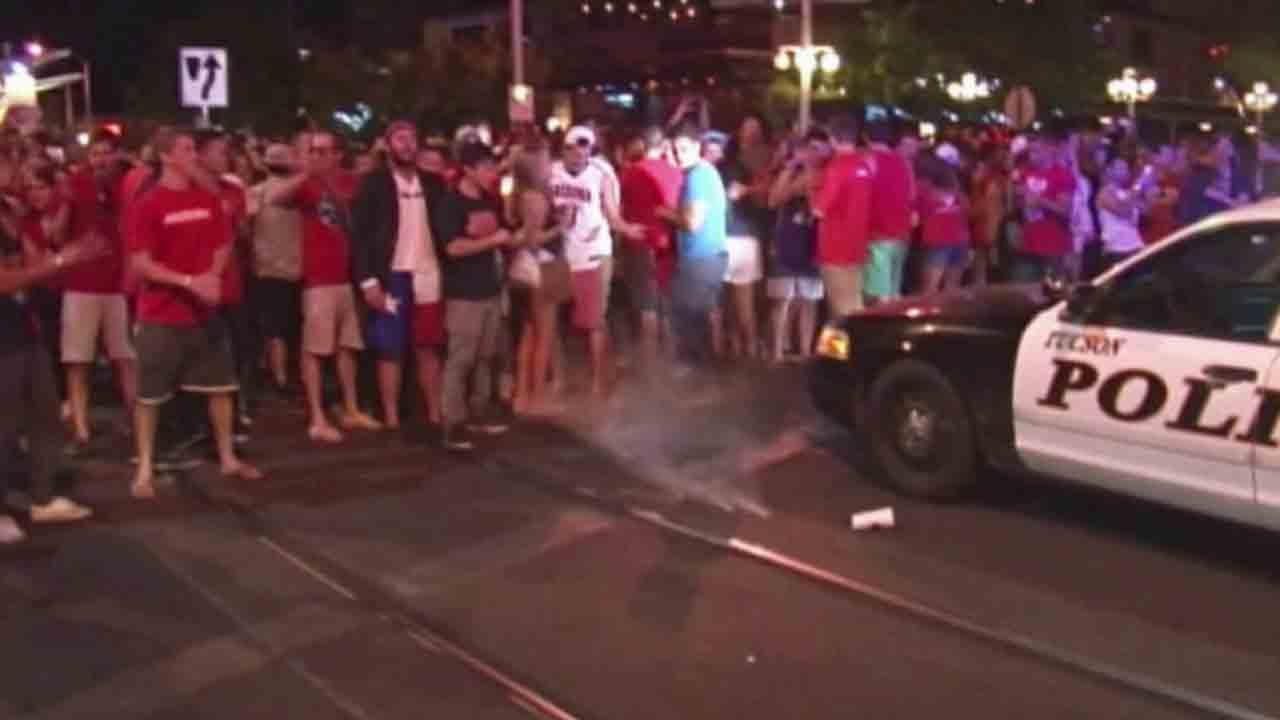 Tucson police shot pepper spray at several hundred fans who took to the streets and threw beer bottles and firecrackers at officers after the University of Arizona basketball teams overtime loss in the NCAA tournament Saturday, March 29, 2014.