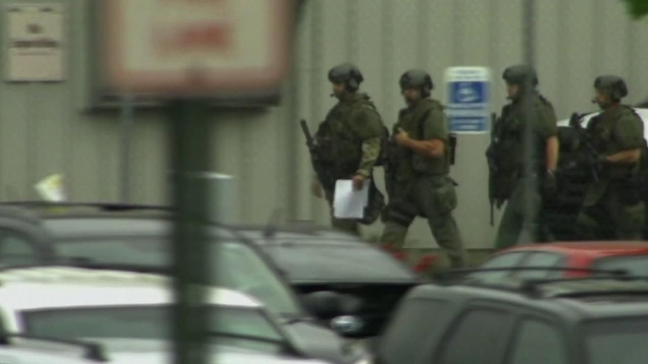 A group of armed officers walk near where a shooting at a FedEx facility occurred on Tuesday, April 14, 2014.