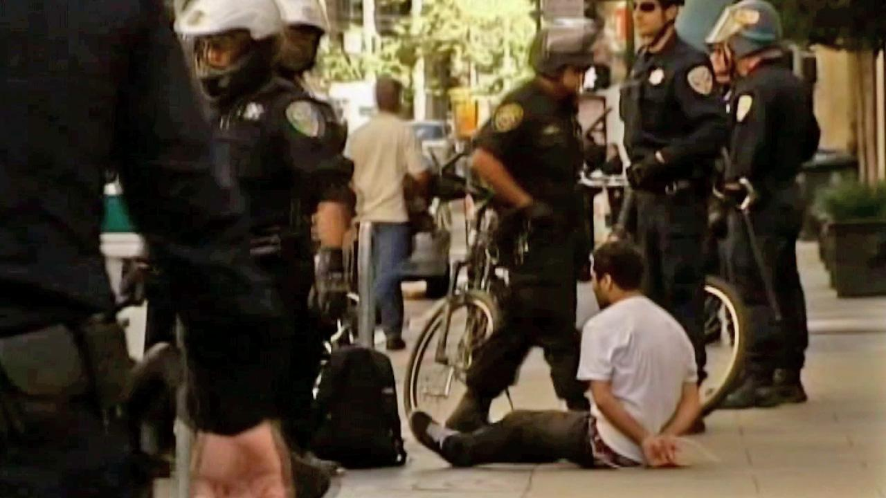 Police are seen with a man on a sidewalk following 12 arrests at an Occupy San Francisco protest on Saturday, Oct. 6, 2012.