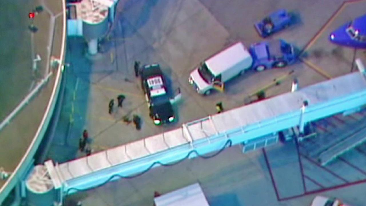 Officials are shown at San Diego Lindbergh Field, where a man was arrested for running onto the tarmac on Thursday, Jan. 17, 2013.