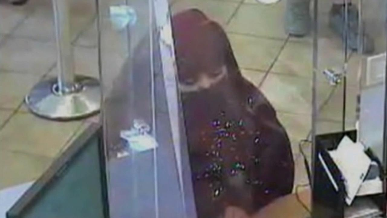 A surveillance photos allegedly shows Elysia Roiz in a maroon Burqa, attempting to rob a bank in National City.