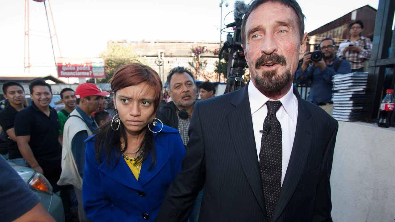 Software company founder John McAfee, right, accompanied by his girlfriend Sam, leaves after a press conference outside the Supreme Court in Guatemala City, Tuesday, Dec. 4, 2012.
