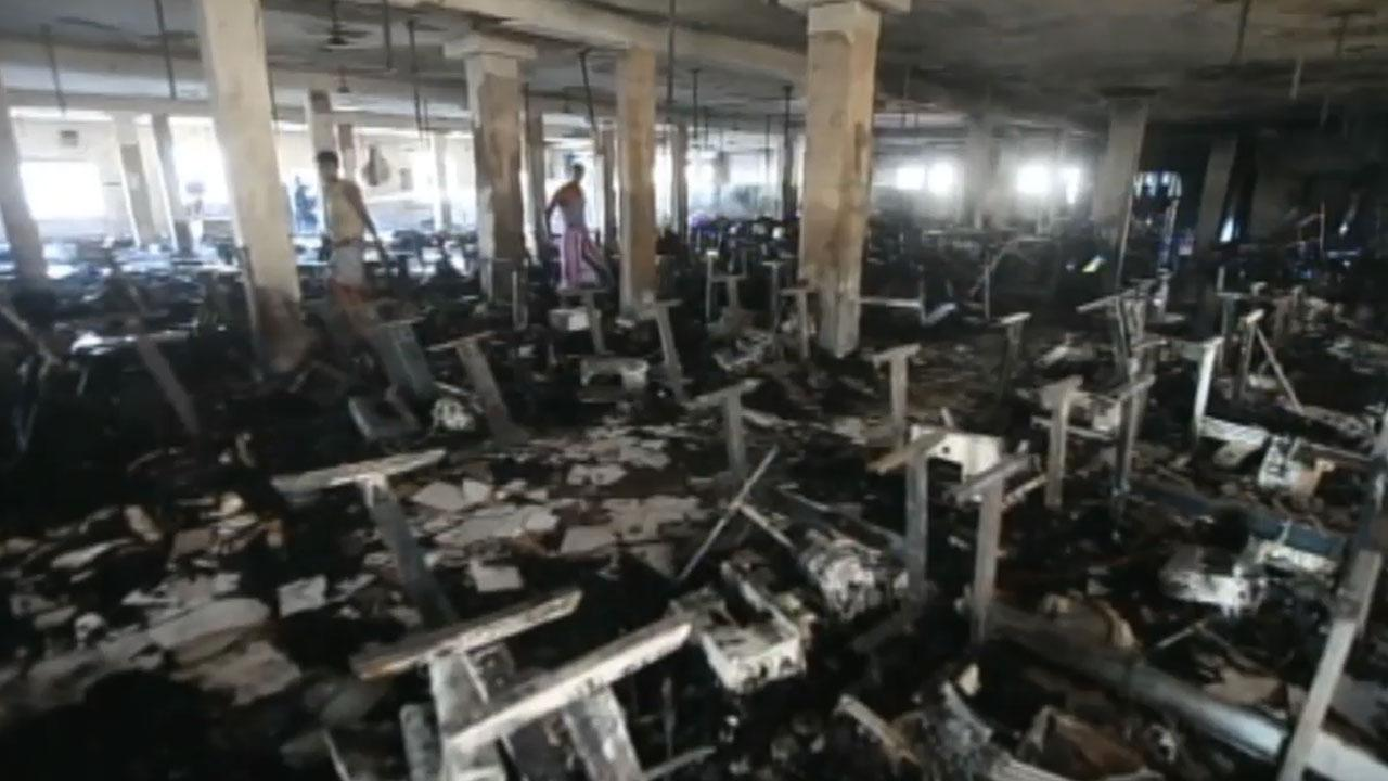 Garment workers look through burned remains inside the Smart Export Garment Ltd. factory where a fire claimed the lives of seven female workers in Dhaka, Bangladesh, Saturday, Jan. 26, 2013.