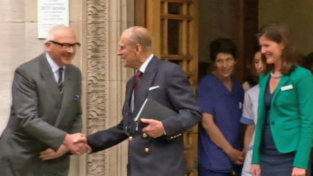 Prince Philip shakes hands with people as he leaves a hospital in London Monday, June 17, 2013.