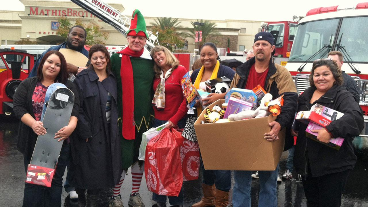 Garth the Elf poses with Impact Solutions employees at the Stuff-A-Bus toy drive at Mathis Brothers Furniture in Ontario on Friday, Nov. 30, 2012.