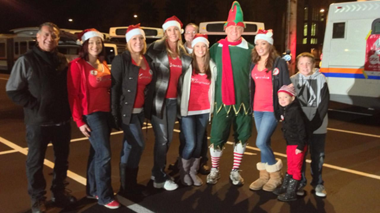Garth the Elf poses with workers from Kimmies Coffee Cup at the Stuff-A-Bus toy drive at the Honda Center in Anaheim on Friday, Dec. 21, 2012.