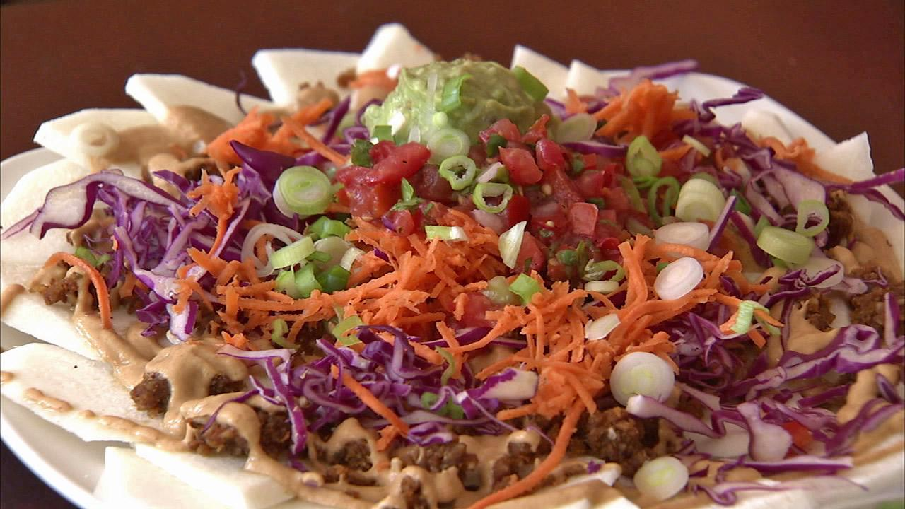 A plate of Sun Cafe nachos -- with raw jicama chips, sun-dried tomato chorizo, cashew cheese, guacamole, pico de gallo and green onion -- is seen in this undated photo.