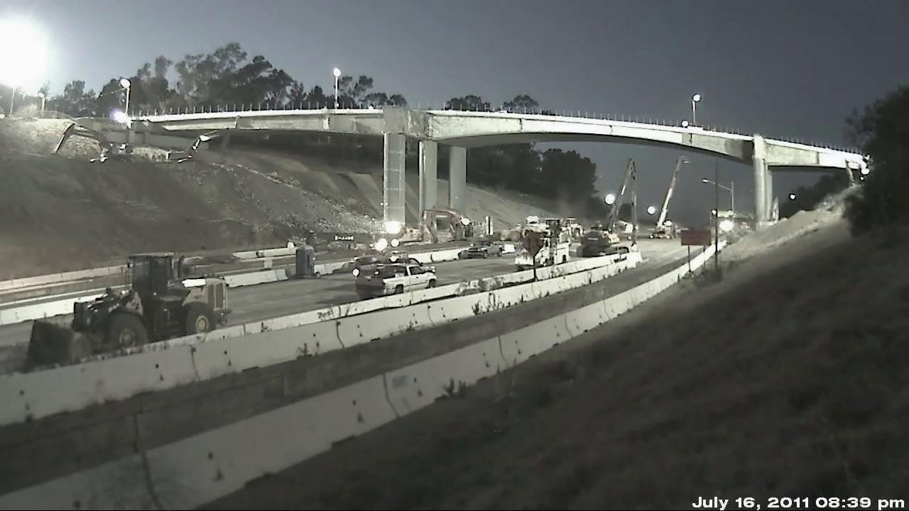 Construction crews work on taking apart the south side of the Mulholland Bridge after the 405 Freeway closed at midnight on July 16, 2011.