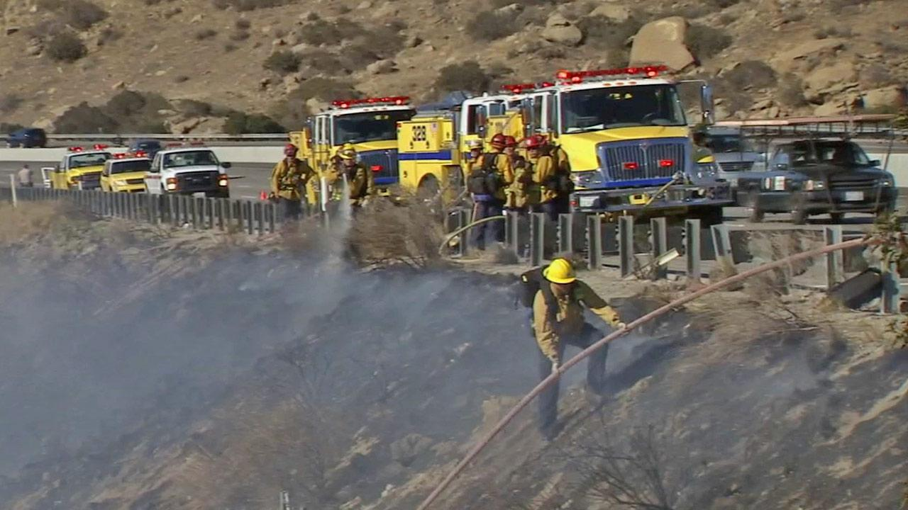 Firefighters are shown battling a brush fire along a hillside in this undated file photo.