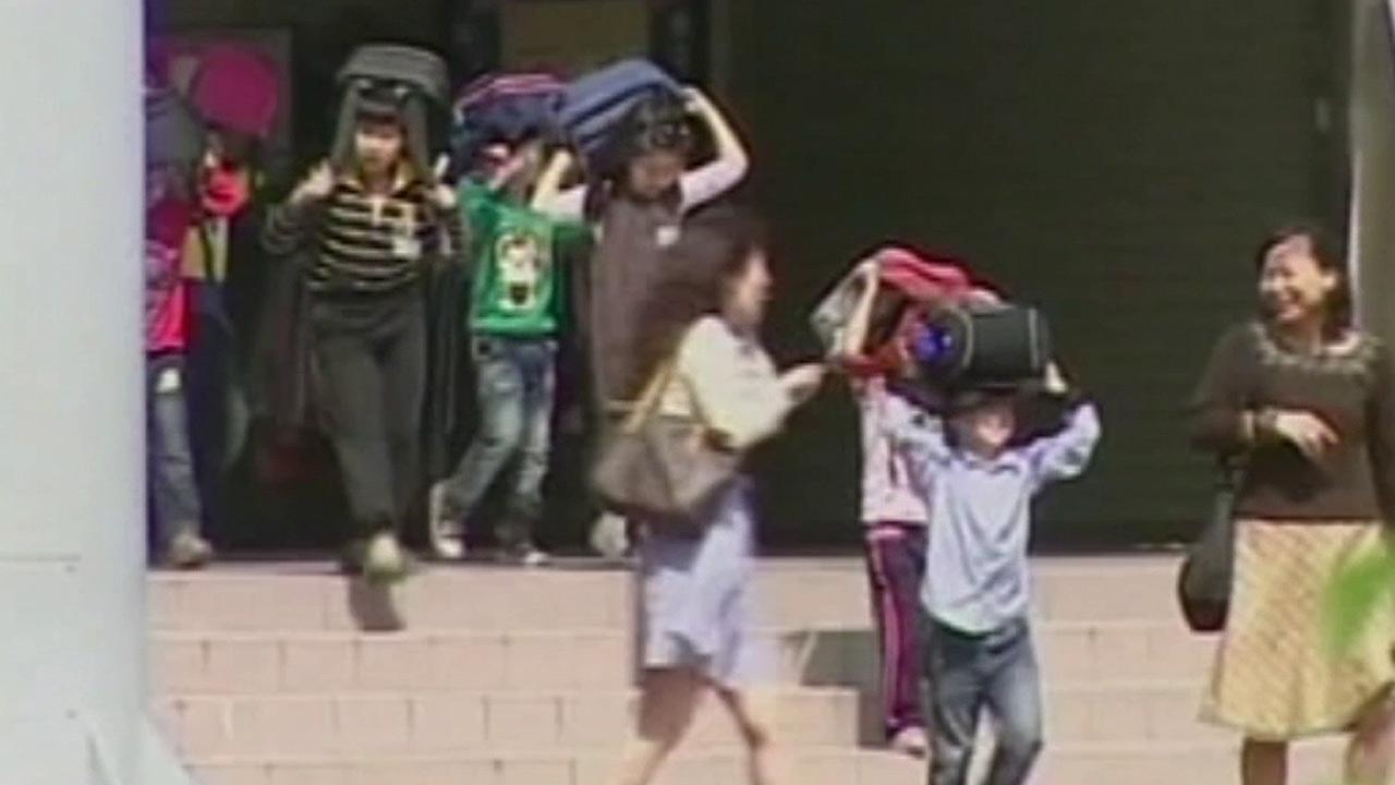 Children are seen leaving a building following an earthquake that struck central Taiwan on Wednesday, March 27, 2013.