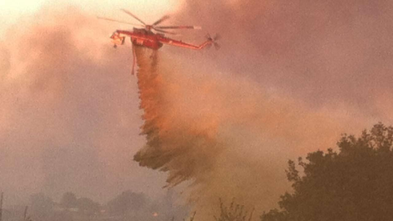A helicopter makes a drop over a fire in Murrieta on Sunday, Sept. 23, 2012.