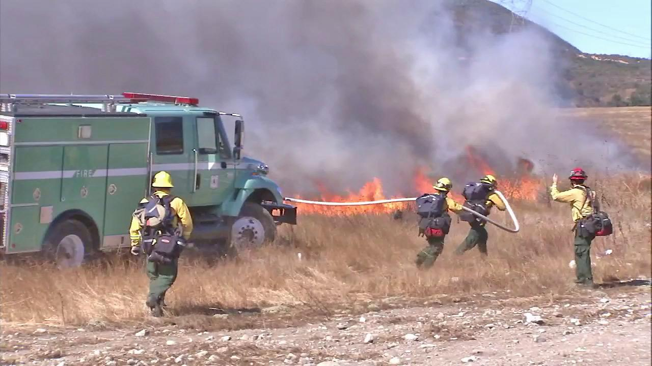 Fire crews are seen battling a blaze off the 15 Freeway in Fontana on Friday, Oct. 26, 2012.