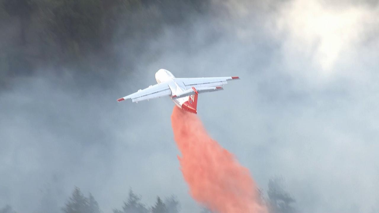 An aircraft drops fire retardant on a wildfire burning in Kern County near Frazier Mountain Park Road and the Interstate 5 Freeway on Wednesday, May 15, 2013.
