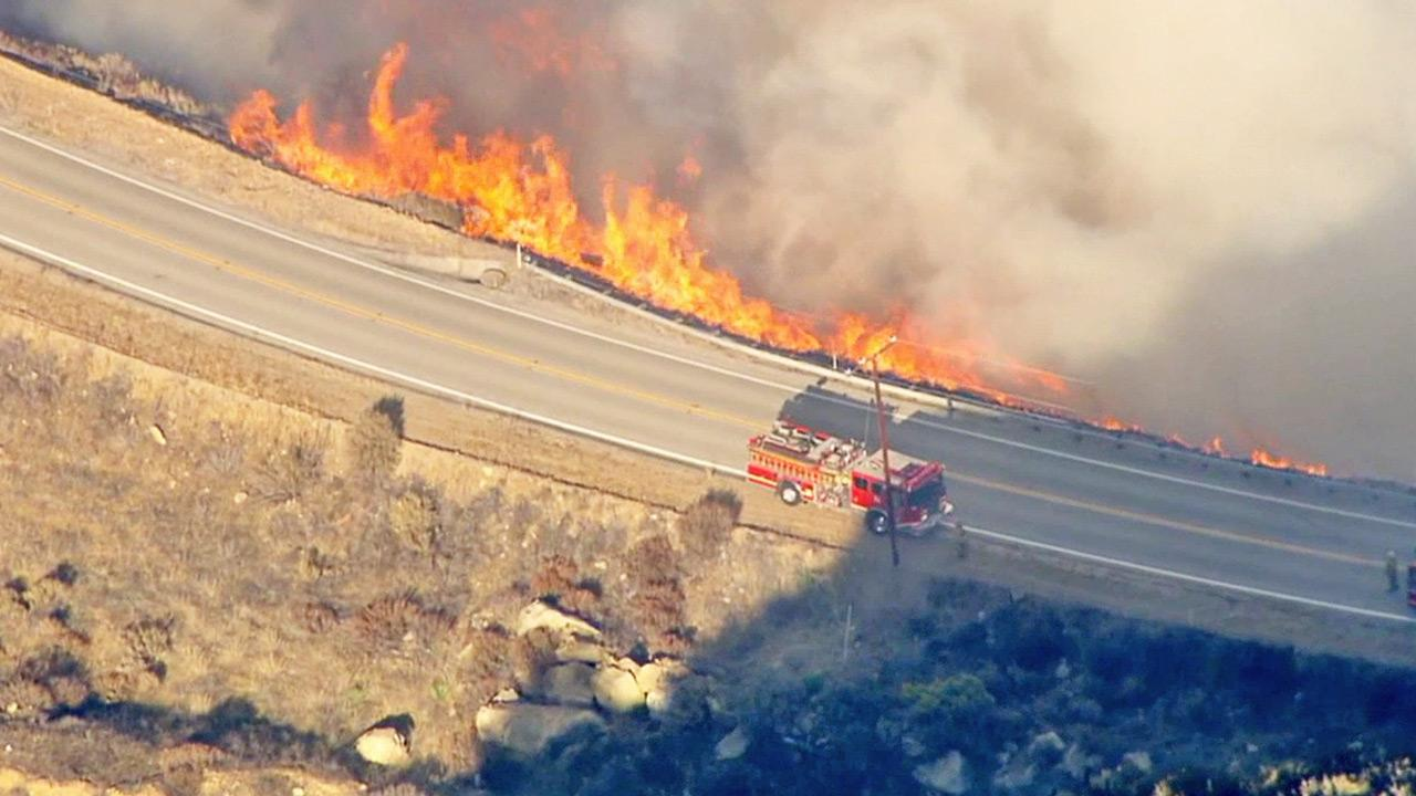 Flames shoot up along a road in the Santa Clarita area on Friday, Aug. 9, 2013.