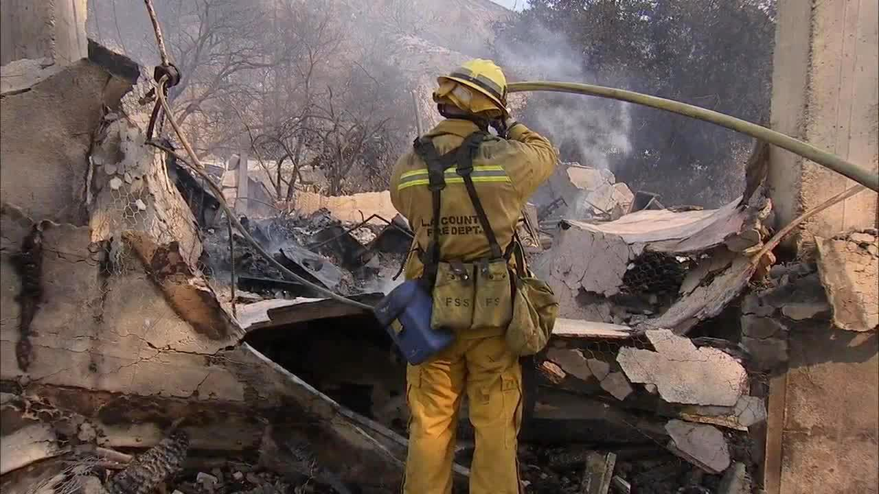 Firefighters are seen dousing flames on a house destroyed by a brush fire burning in the foothills above the Glendora and Azusa area on Thursday, Jan. 16, 2014.