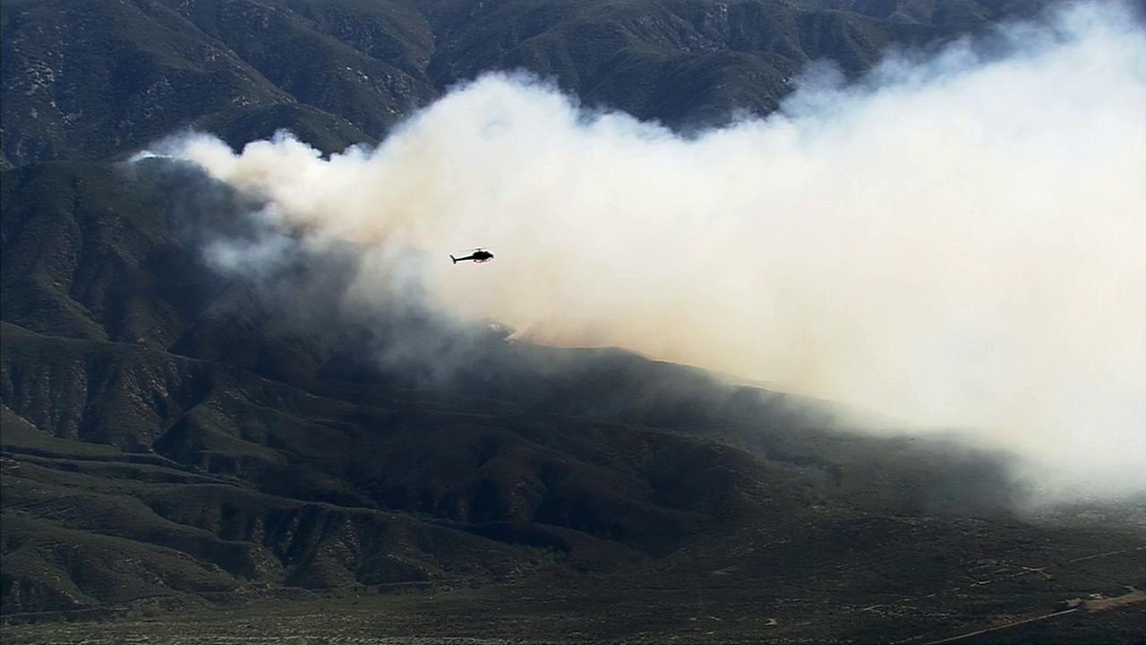 A helicopter flies near a brush fire that erupted north of Rancho Cucamonga Wednesday, April 30, 2014.