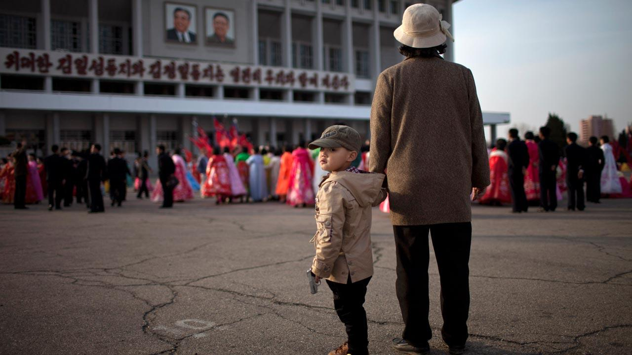 A boy holds a toy gun while his grandmother watches a mass folk dance in front of the Pyongyang Indoor Stadium in Pyongyang, North Korea, Monday, April 15, 2013.