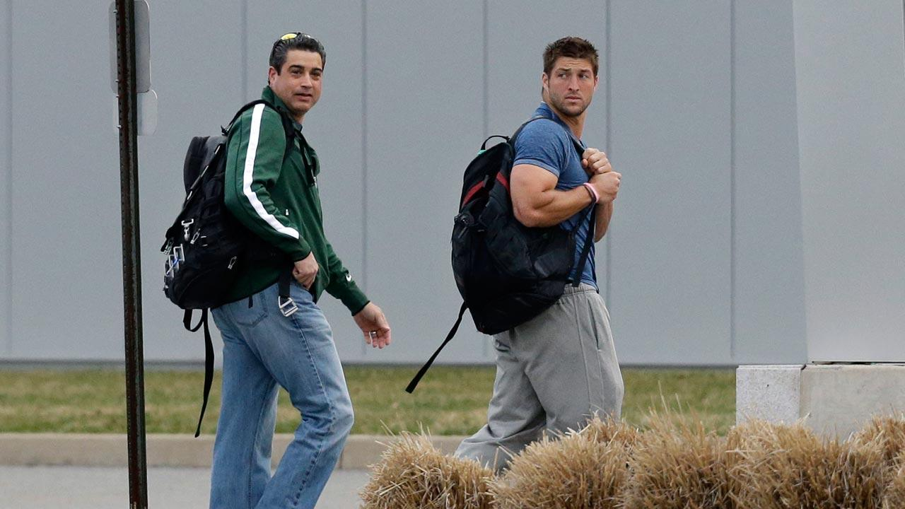 New York Jets quarterback Tim Tebow, right, walks with former NFL punter, now Jets assistant special teams coach, Louis Aguiar, as they arrive at the New York Jets practice facility in Florham Park, N.J., Monday, April 15, 2013.
