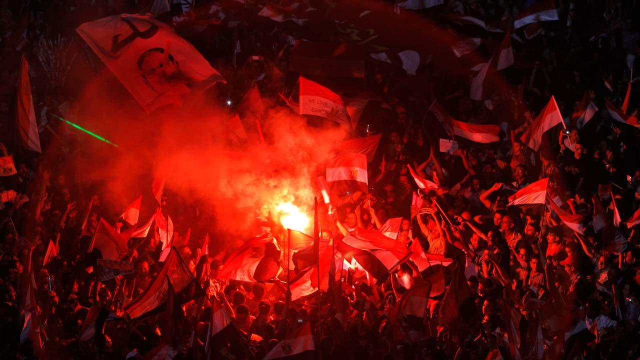 Opponents of Egypts Islamist President Mohammed Morsi celebrate as they light flares and wave national flags and his picture with Arabic reads, leave, in Tahrir Square