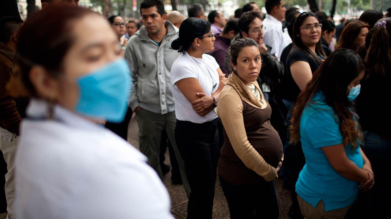 A pregnant woman waits with others outside her office after evacuating due to an earthquake in Mexico City, Wednesday, Aug. 21, 2013.