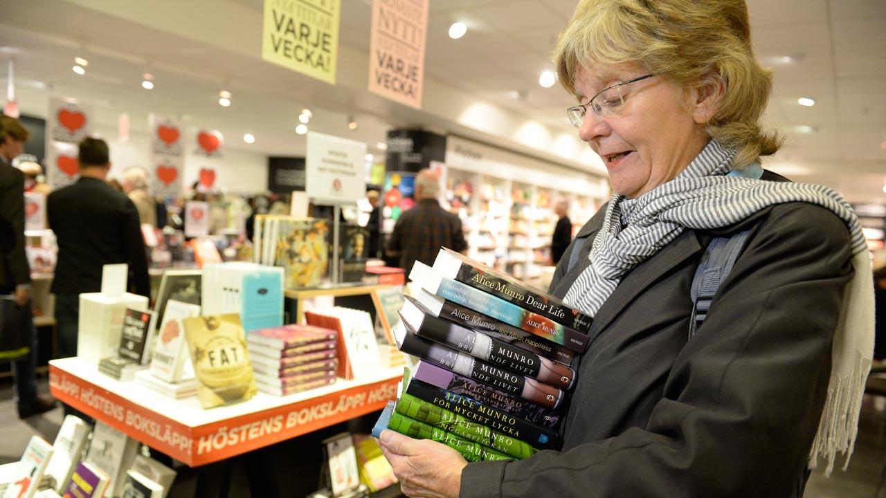 Monica Nordberg collects an armful of books by newly announced 2013 Nobel literature prizewinner, Alice Munro of Canada, at a Stockholm bookstore Thursday Oct. 10, 2013. Customers waited for the prize announcement to be first in line.