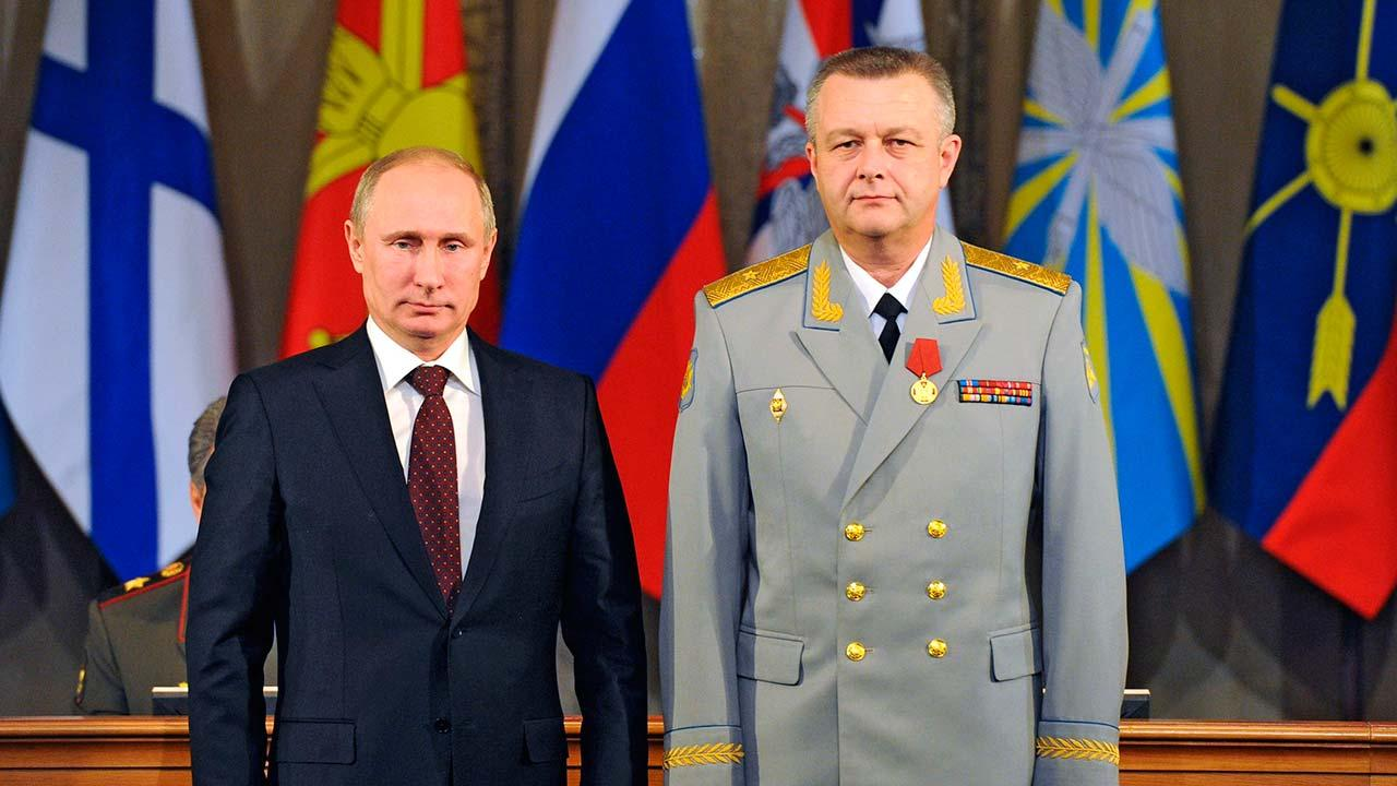 Russian President Vladimir Putin, left, presents a medal to Commander of the Russian Military Air and Space Defense Forces Alexander Golovko