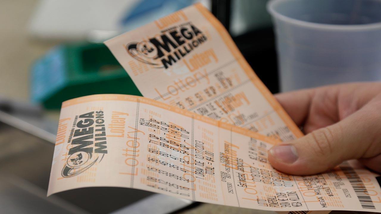 Scott Hoormann holds two Mega Millions lottery tickets he purchased at Energy Express Monday, Dec. 16, 2013, in St. Louis. The Mega Millions jackpot now stands at an estimated $636 million with the next drawing set for Tuesday night.