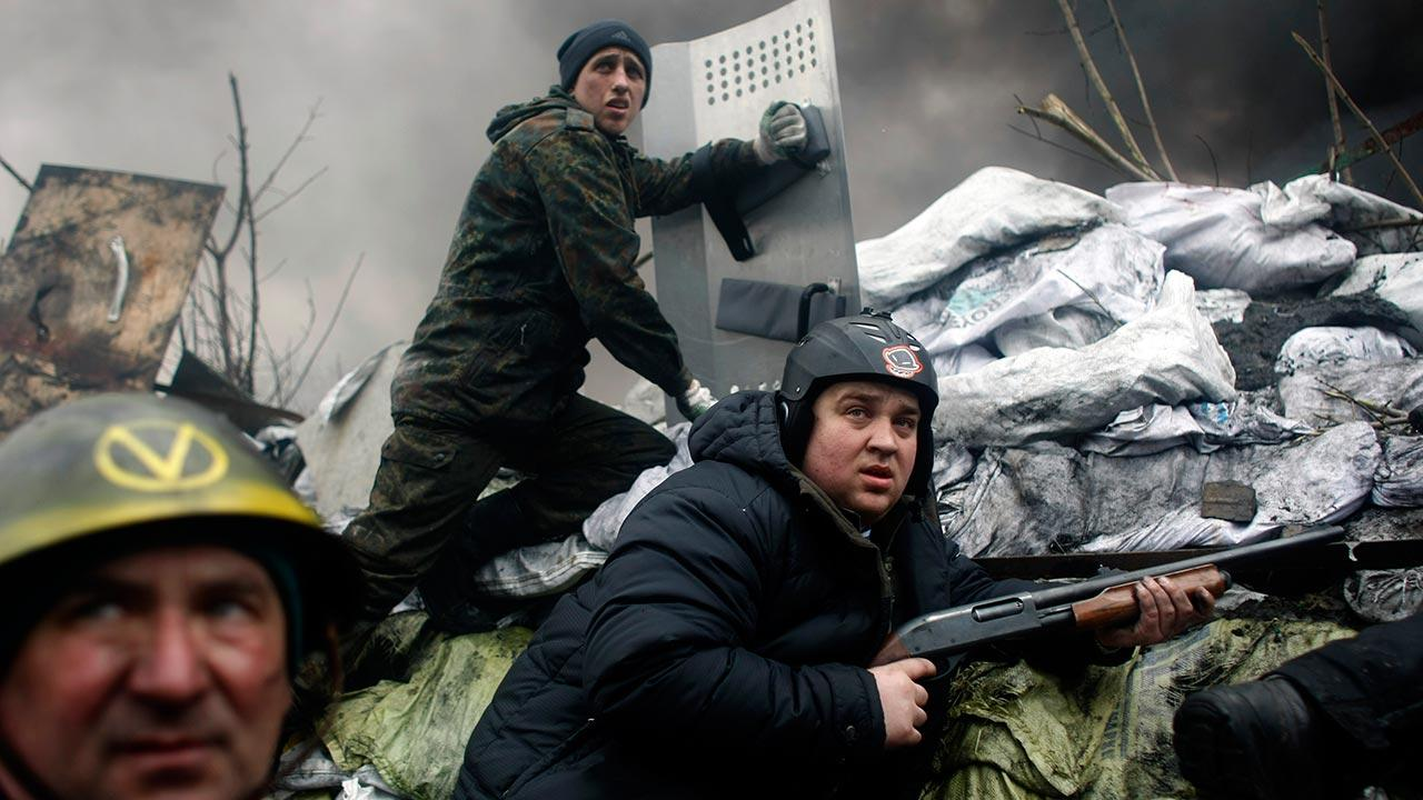 An anti-government protester holds a firearm as he mans a barricade on the outskirts of Independence Square in Kiev, Ukraine, Thursday, Feb. 20, 2014.