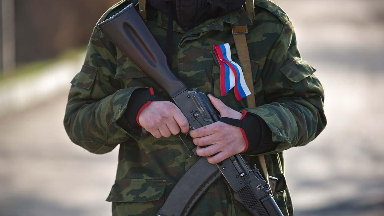 A masked member of the newly formed army of Crimea, wearing a ribbon in the colors of the Russian flag, holds his weapon at the gate to a military base in Simferopol, Ukraine, Thursday, March 13, 2014.