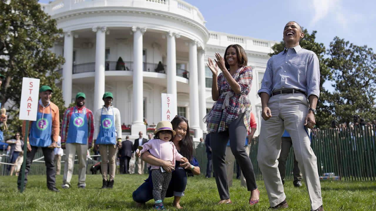 President Barack Obama and first lady Michelle Obama cheer and laugh as they host the annual White House Easter Egg Roll, Monday, April 21, 2014