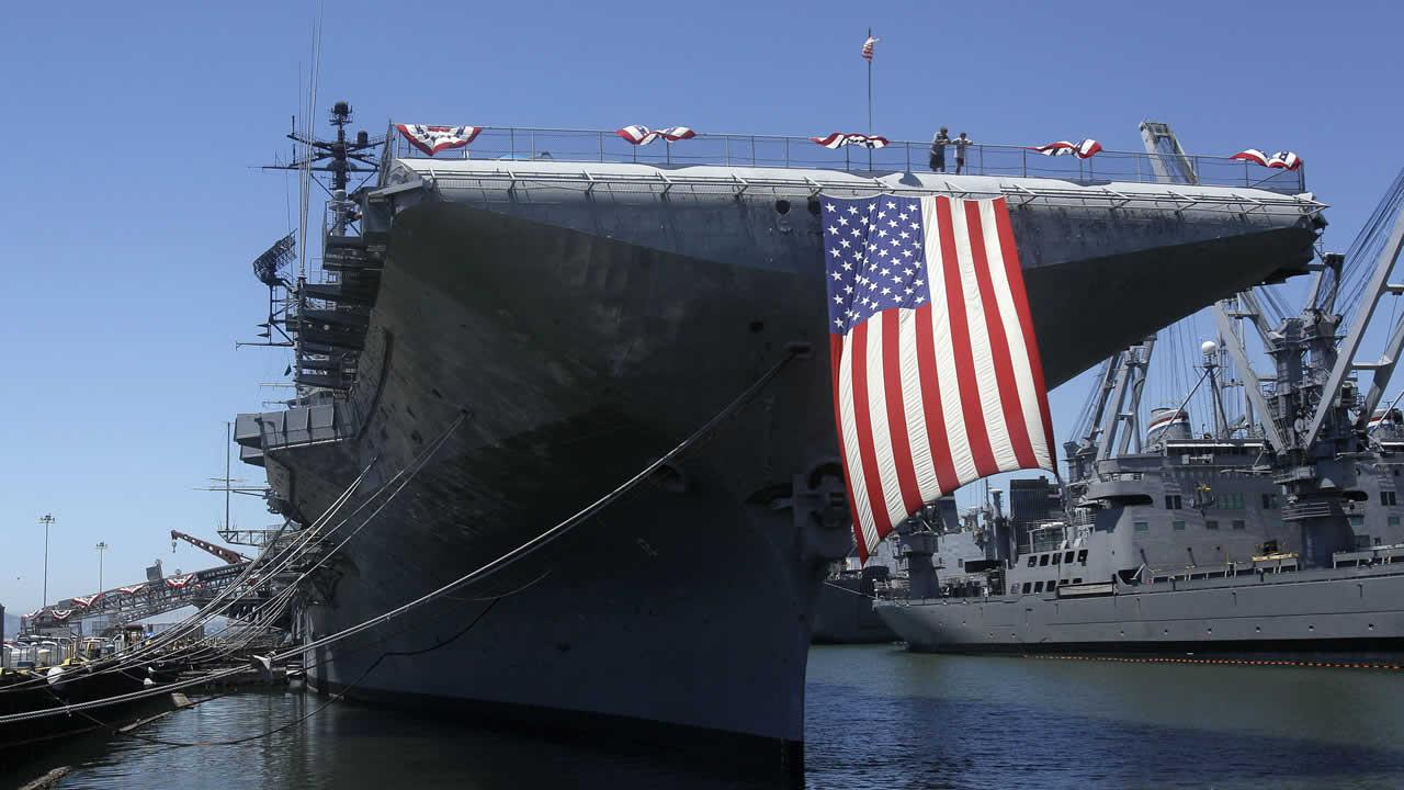 A large American flag hangs from the flight deck of the USS Hornet during Fourth of July festivities in Alameda, Calif., Monday, July 4, 2011.