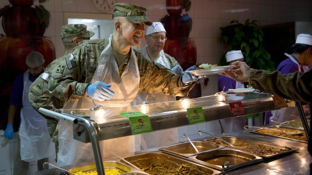 A U.S. Army officer serves Thanksgiving dinner to a comrade at a dining facility at his base in Kabul, Afghanistan, Thursday, Nov. 28, 2013. Its the 12th Thanksgiving in Afghanistan for U.S. troops. (AP Photo/Anja Niedringhaus)