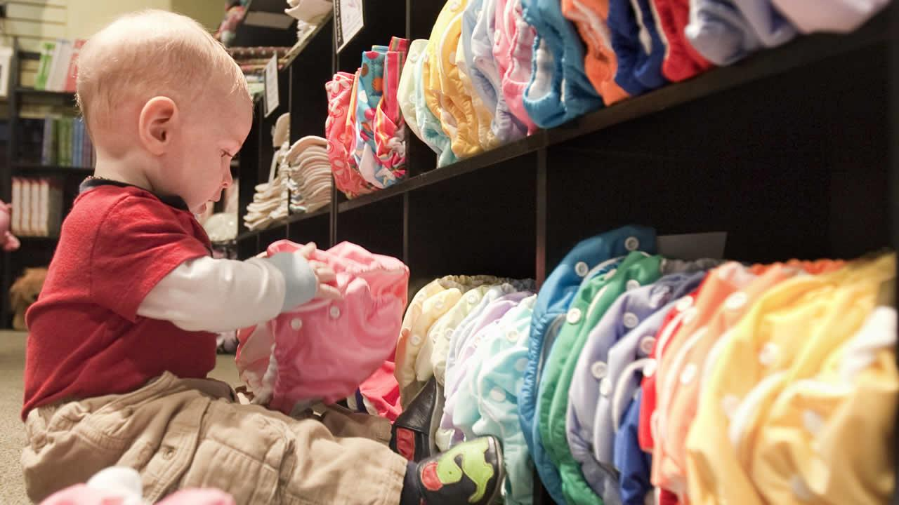 Int his Feb. 5, 2009 photo, 8-month-old Ezra Bird occupies himself with cloth diapers at the Circle Me store in Lincoln, Neb.