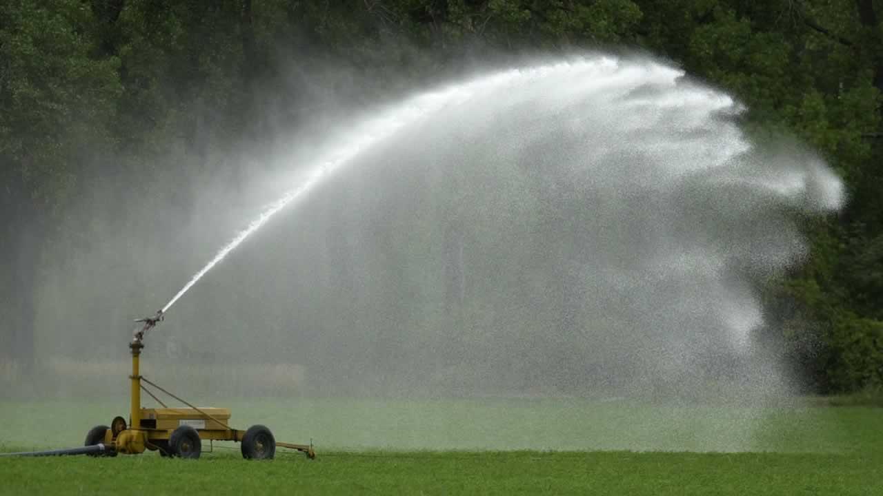 A sprinkler sprays water onto a hay field near Hoxie, Kan., Aug. 28, 2003.